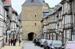 Fachwerkbebauung in Goslar, Breite Strasse - im Hintergrund das Breite Tor, Teil der historischen Stadtbefestigung aus dem 16. Jahrhundert.