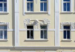 Jugendstilgebäude in Halberstadt - Stuckdekor, Kopf Relief - florales Dekor, Blüten / Blätter.