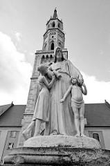 Jesus-Skulptur vor der Pfarrkirche Mariä Himmelfahrt; Ersterwähnung im 13. Jahrhundert, im Hussitenkrieg 1429 zerstört - wiedererrichtet als dreischiffiger gotischer Bau - Zerstörung im 30 jährigen Krieg; Wiederaufbau 1692 in spätgotischem Baustil.