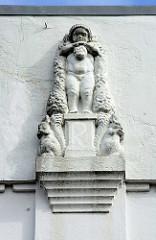 Historische Industriearchitektur im Hamburger Stadtteil Eimsbüttel  - Relieffigur unter dem Flachdach / Putte, nacktes Kind - Eichhörnchen.