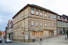 Verfallenes, renovierungsbedürftiges Fachwerkgebäude in Blankenburg; mit Holzplatten vernagelte Schaufenster.