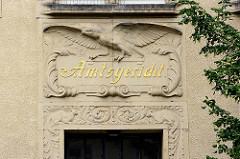 Inschrift Amtsgericht - sitzender Adler mit ausgebreiteten Schwingen - Arabesken und Tierfiguren; Eingang Amtsgericht Goslar.