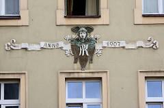 Fassadenschmuck von einem Wohnaus in der  Altstadt von Świdnica / Schweidnitz; Hermes, Relief Kopf - Helm mit Flügeln; Jugenstilblüten - Schriftband Anno 1907.