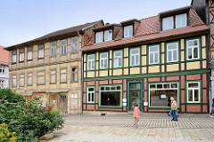 Verfallenes, renovierungsbedürftiges Fachwerkgebäude in Blankenburg; mit Holzplatten vernagelte Schaufenster. Daneben ein restauriertes / neugebautes Fachwerkgebäude, neu + alt.