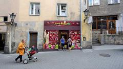 Eisdiele / Eisverkauf mit bunter Fassade, Eissorten - Kinder vor dem Geschäft, graue Hausfassaden in Kłodzko / Glatz.