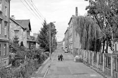 Wohngebiet - Gewerbegebiet mit Industriegebäude in Świdnica / Schweidnitz - ein Paar geht auf der Strassenmitte; Schwarz-Weiß-Fotografie aus