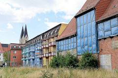 Rückseite von mehrstöckigen Häusern in Halberstadt - Wohnhaus mit Balkons, leerstehendes Fachwerkhaus mit Planen geschützt.