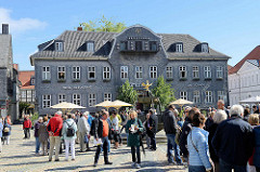 Touristen auf dem Marktplatz von Goslar - Blick zum Kaiserringhaus, ehem. Kämmereigebäude - an dessen Giebel ist eine Uhr. Viermal am Tag öffnen sich die drei darunter befindlichen Türen und eine Figurengruppe in Bergmannstracht erscheint. Diese b