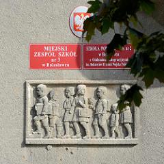 Steinrelief an der Hausfassade eines Schulgebäudes - Schulkinder mit Ranzen und Schultaschen - Jungen und Mädchen; Architektur in Bunzlau / Bolesławiec.
