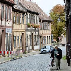 Fachwerkhäuser und Kopfsteinpflaster; Blumenkästen mit Geranien vor den Fenstern; Strasse in Blankenburg / Harz.