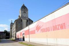 Expressionistische Industriearchitektur - Merino Spinnerei / Weberei in Bunzlau / Bolesławiec, erbaut 1926 - Industrieruine, leerstehendes Gebäude. Farbige Hausfassade - Werbung eines Gewerbebetriebes.
