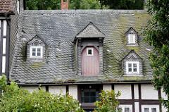Fachwerk / Hausdach mit  Schiefereindeckung - Mansarden und Dachluke mit Holztür.