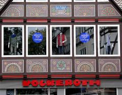 Neubau mit Schnitzereien - Fassade Ladengeschäft; Männer Mode.