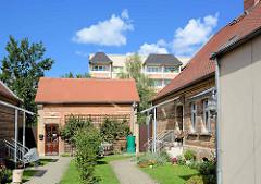 Innenhof mit Hauszugängen / historische Doppelhäuser; Kletterrosen am Schuppen - im Hintergrund mehrstöckige Wohnblocks.
