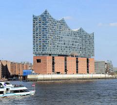 Blick über die Norderelbe zur Hamburger Elbphilharmonie - Bug eines Fahrgastschiffs mit Hamburg Flagge.
