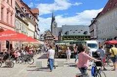 Wochenmarkt am Marktplatz von Quedlinburg - Verkaufsstände mit Obst und Gemüse; Cafés und Restaurant mit Tischen auf der Strasse - Gäste sitzen unter Sonnenschirmen in der Sonne; im Hintergrund das Rathaus und die Marktkirche / St. Benedikt Kirch
