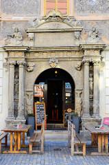 Historische Architektur in Kutná Hora / Kuttenberg - aufwändige Fassadenmalerei, Eingang mit Säulen und Wappendekor; jetzt Restaurant mit Holztischen vor der Tür.