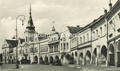 Historisches Motiv vom Marktplatz in Melnik - Arkadengang und parkende PKW, Lastwagen vor dem Rathaus der Stadt.