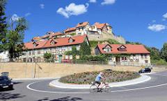 Fahrradfahrer im Kreisverkehr - mit Blumen bepflanztes Rondell; im Hintergrund Gebäude auf dem Münzenberg in Quedlinburg.