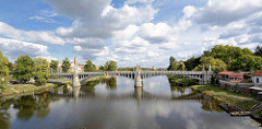 Architektur in Nymburk / Neuenburg an der Elbe - Brücke über den Fluss, Brückengeländer mit Pfeiler / Kandelaber - im Hintergrund die Altstadt und das Wasserkraftwerk - blauer Himmel mit weissen Wolken.