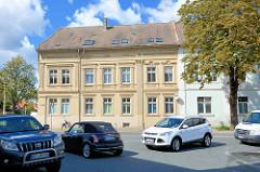 Straßenkreuzung, Autoverkehr in Aschersleben - Gründerzeitgebäude, kannelierte Säulen und Stuckdekor an der Hausfassade.