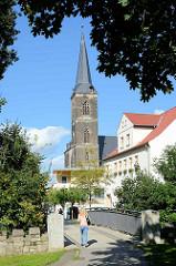 St. Stephani Kirche in Aschersleben; gotische Hallenkirche, erbaut von 1406 - 1507. Im Vordergrund eine Fussgängerbrücke über die Eine.