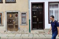 Alt + Neu, Haustüren in Quelinburg - re. restauriert mit gestrichener Fassade - lks grauer Rauputz und abblätternde Farbe / leerstehendes Gebäude.
