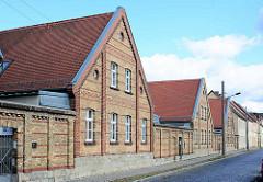 Architektur in Aschersleben - Ziegelhäuser, mit roten Ziegelbändern als Fassadengestaltung - Doppelhäuser mit Siedlungscharakter, hohe Ziegelmauer.