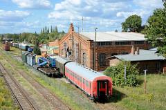 Blick auf das Bahngelände vom ehem. Bahnbetriebswerk BW Aschersleben; Bahnwaggons stehen auf den Gleisen - Lokschuppen, historische Backsteinarchitektur.