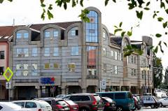 Moderne Architektur / Bankgebäude am Marktplatz von Nymburk / Neuenburg an der Elbe in Tschechien; Eckgebäude, parkende Autos.