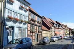 Restaurierte Fachwerkgebäude mit farbig abgesetzter Hausfassade - Blumenkästen mit Geranien vor den Fenstern - Ballstraße in Quedlinburg.