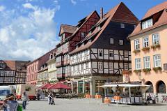 Historische Bebauung - mehrstöckige Fachwerkhäuser am Marktplatz von Quedlinburg; Imbisswagen und Aussengastronomie mit Sonnenschirmen auf der Straße.