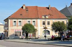 Platz in Kutná Hora / Kuttenberg; BewohnerInnen sitzen auf Bänken in der Sonne.