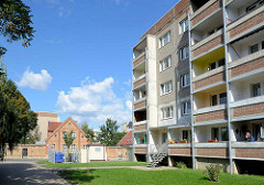 Alt + neu /  Architektur in Aschersleben; mehrstöckiger Wohnblock, Plattenbau mit Balkons - im Hintergrund historisches Doppelhaus, Ziegelgebäude mit Backsteinmauer.