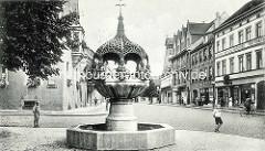 Altes Bild vom Hennebrunnen in Aschersleben; die Brunnenanlage zeigt eine durch einen Baldachin überdachte gegliederte Säule, auf der acht eigenartige Bronzeputten sitzen. Der Brunnen wurde von Georg Wrba entworfen und 1906 eingeweiht.