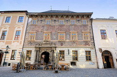 Historische Architektur in Kutná Hora / Kuttenberg - aufwändige Fassadenmalerei, Eingang mit Säulen und Wappendekor.