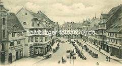 Altes Bild vom Quedlinburger Marktplatz - Marktstände in einer Reihe; Geschäfte - im Vordergrund Fassadenaufschrift Drogen, Colonialwaaren, Cigarren, Farben, Tapeten, Wachstuch; Pferdefuhrwerke stehen am Strassenrand.