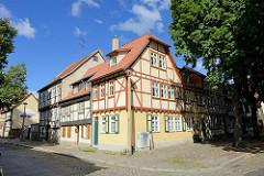 Restaurierte Wohnhäuser in Quedlinburg - Fensterläden; obere Stockwerke mit sichtbarer Fachwerkkonstruktion. Kopfsteinpflaster auf Fußweg und Straße.
