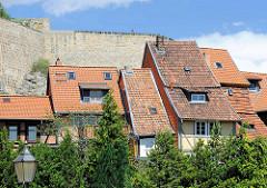 Historische Häuserreihe, Wohnhäuser mit unterschiedlichen Breiten - Architektur in Quedlinburg; dahinter die Schlossmauer vom Schloßberg.