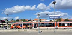 Bahnhof von Aschersleben - ein Zug ist in den Bahnsteig eingefahren, Fahrgäste mit Rädern steigen aus.