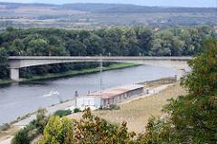 Lauf der Elbe bei Mělník in Tschechien - Lagergebäude am Flußufer, ein Sportboot fährt flussabwärts.