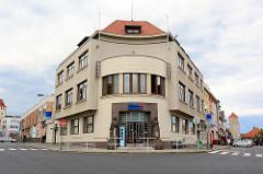 Gebäude der Tschechischen  Sparkasse / Česká spořitelna - Eckgebäude mit rundem Eingangsbereich mit Skulpturen - Architekturfotos aus Mělník.