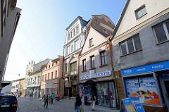 Geschäftsstraße in Dvůr Králové nad Labem / Königinhof an der Elbe; Wohnhäuser, Geschäftshäuser mit Einzelhandel in unterschiedlicher Bauhöhe und Architekturform. Fußgänger in der Fußgängerzone.