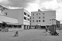Platz in Nymburk / Neuenburg an der Elbe; kubische Architektur, Wohnhäuser - Restaurant mit Aussengastronomie; Kind mit Fahrrad - Frau mit Hund, leere Sitzbänke.