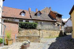 Fachwerkhäuser und enge Gassen mit Kopfsteinpflaster auf dem Münzenberg in Quedlinburg - ehem.  Sitz vom Beneditkinerinnenkloster und St. Marienkirche. Um 1539 wurde das Kloster aufgegeben  und ab 1580 von Handwerkern, fahrenden Leuten und Musiker