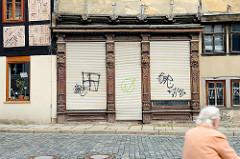 Altes leerstehendes Fachwerkgebäude in Quedlinburg - aufwändig geschnitzte Holzsäulen am Eingang / Geschäftsfenstern.