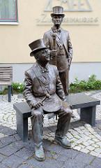 Statuen von zwei Logenbrüdern in freimaurerischer Kleidung vor dem Café Zum Freimaurer in Quedlinburg; der Stuhlmeister sitzt, und hinter ihm steht der Zeremonienmeister - Metallgestalter Jochen Jo Müller.