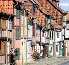 Fachwerkhäuser - Hausfassaden in Quedlinburg; Hauswände mit Dachziegeln verkleidet, moderne Strassenlaternen.