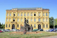 Historische Architektur in Dvůr Králové nad Labem / Königinhof an der Elbe; Gebäude vom städtischen Gymnasium - im Vordergrund ein Denkmal des Widerstandes.
