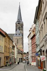 Strasse mit Geschäften - Eisladen mit Werbefahnen an der Hauswand - Kirchturm der St. Stephani Kirche in Aschersleben; gotische Hallenkirche, erbaut von 1406 - 1507.